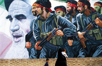 A woman passes a poster of the Khomeini and revolutionary guards, Iran.